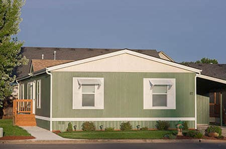Nice and large olive colored manufactured home with carport and staircase.