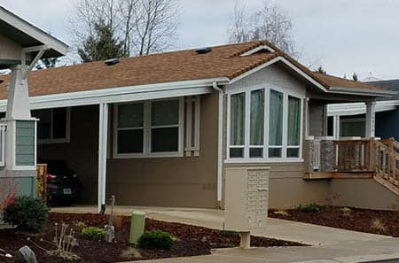 Tan Manufactured home with a nice bay window. The home is located in in a manufactured home community.